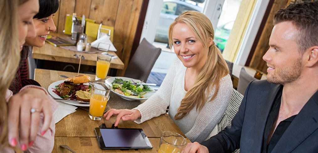 Woman With Digital Tablet Having Food With Colleagues